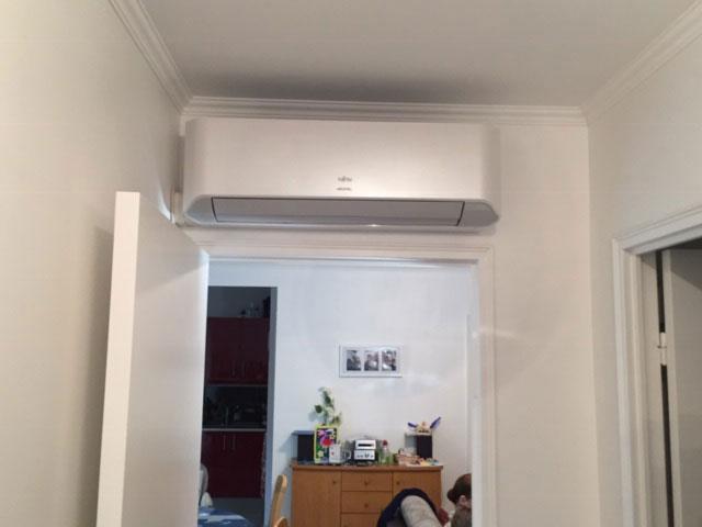 unité de clim intérieure au-dessus d'une porte dans un logement