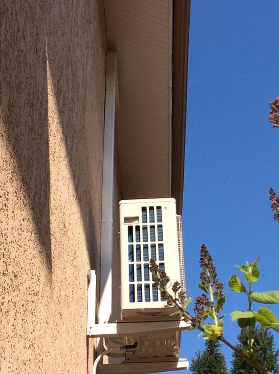groupe clim extérieur accroché à la façade d'une maison