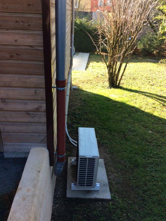 groupe de climatisation extérieur posé dans le jardin d'une maison