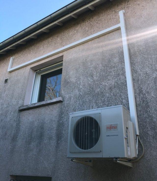 bloc extérieur système de climatisation fujitsu atlantic accroché à la façade d'une maison